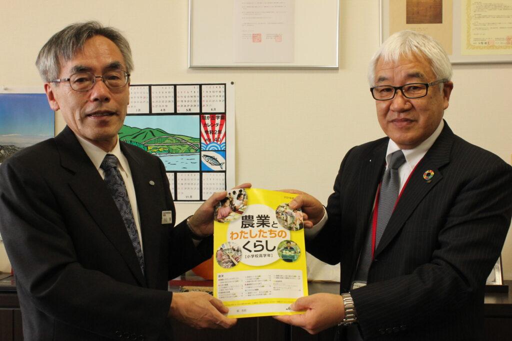高橋本部長(右)から目録を受け取る小山 淳教育長(左)
