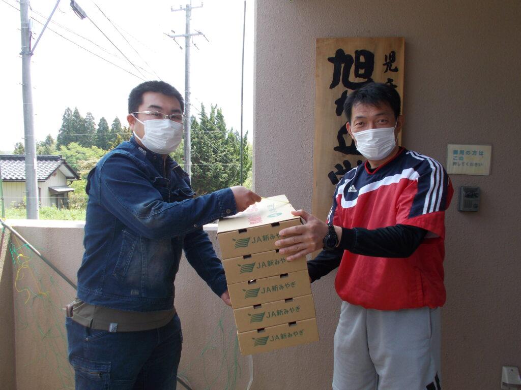 旭が丘学園職員(右)に「気仙沼いちご」を手渡す小野寺正弘さん(左)