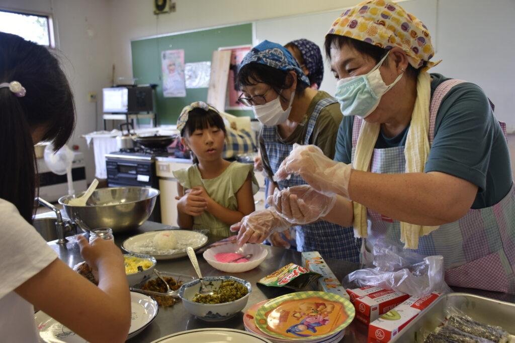 学童の子供たちにおにぎりの作り方を教える石川美知子部長(右)