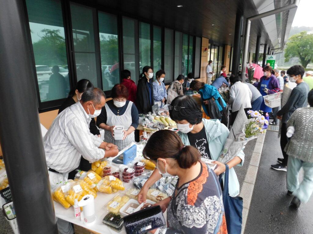 「朝市」にて、特産品を買い求める来場者(右)(8月13日、宮城県南三陸町で)