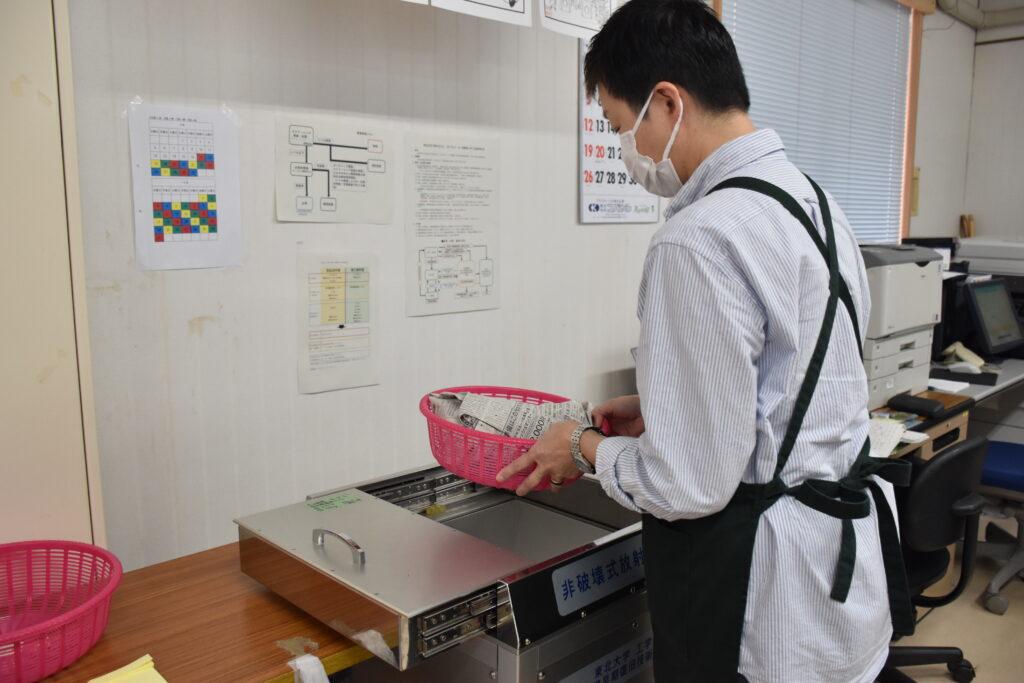 マツタケを放射能測定器に入れるJA担当者(27日、宮城県気仙沼市で)